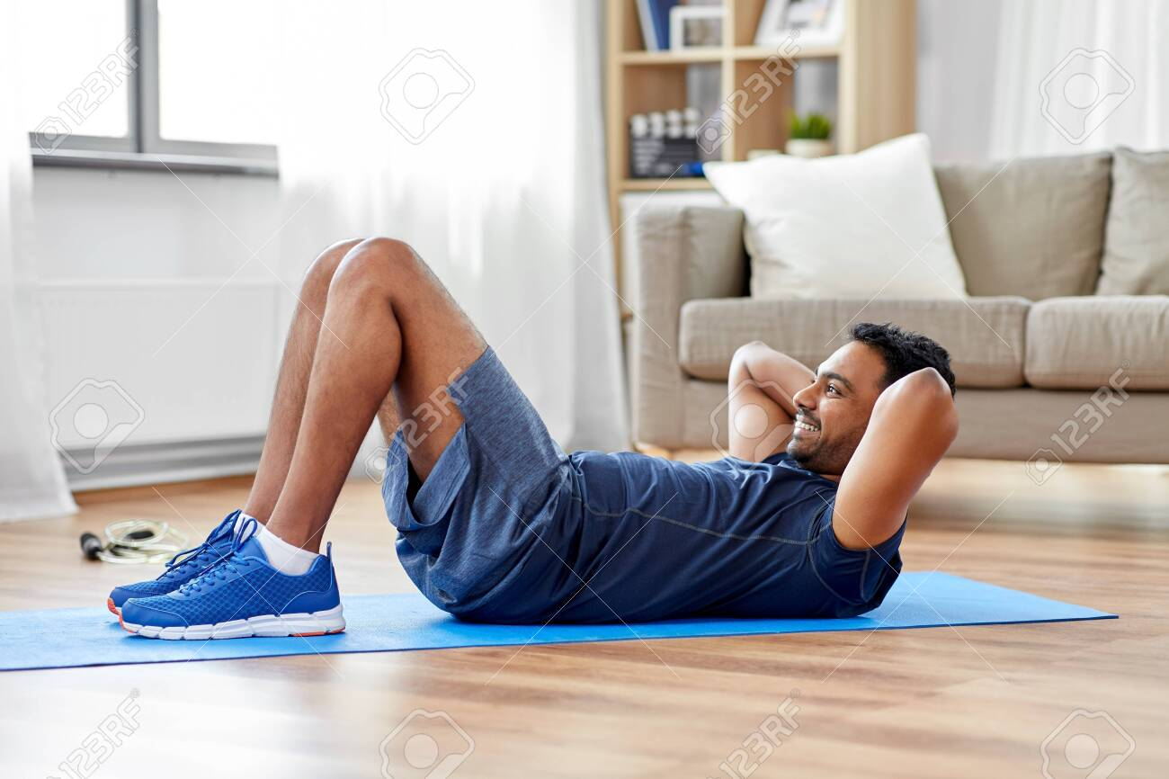 sport, fitness and healthy lifestyle concept - indian man making abdominal exercises at home - 125557720
