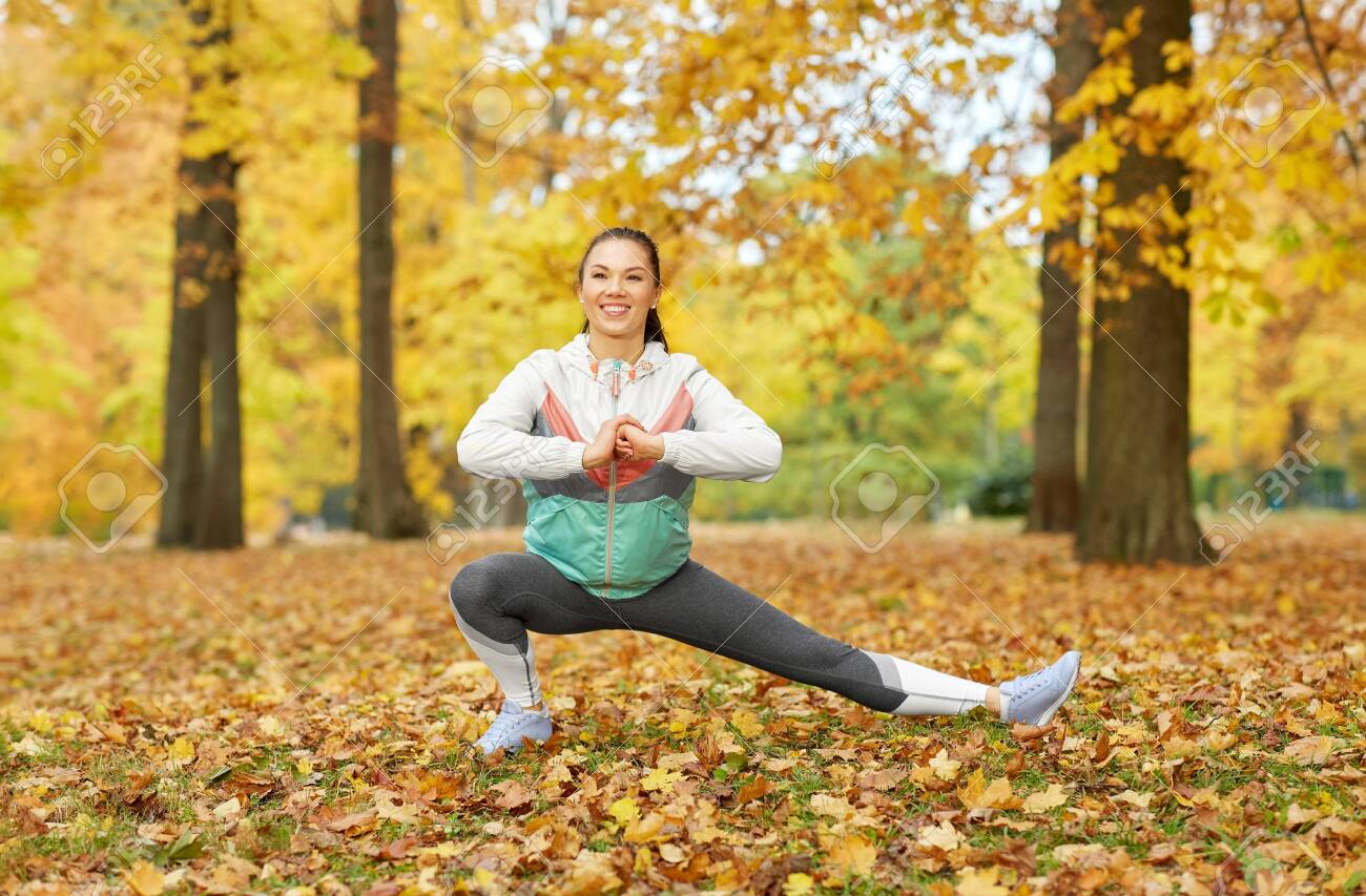 Young woman doing sports at autumn park - 125731416