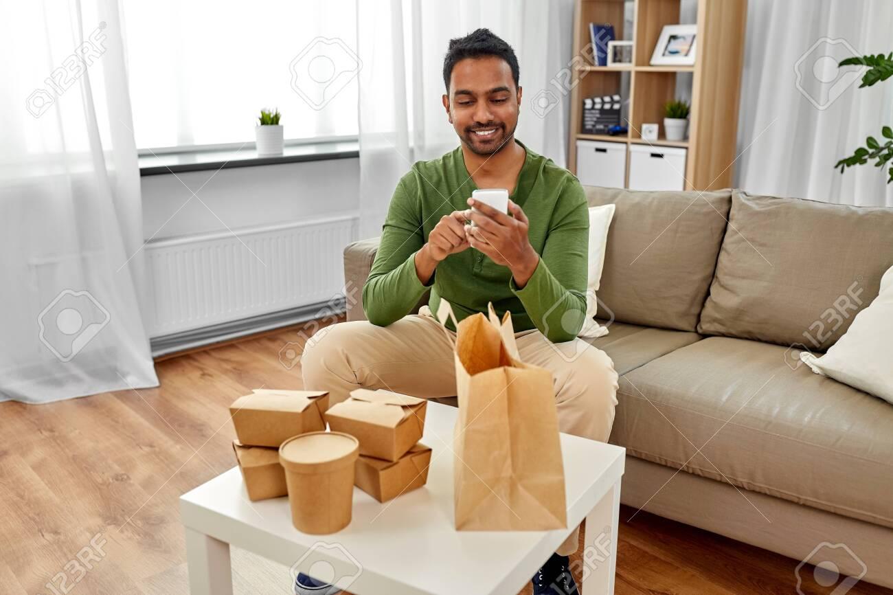 indian man checking takeaway food order at home - 126481425