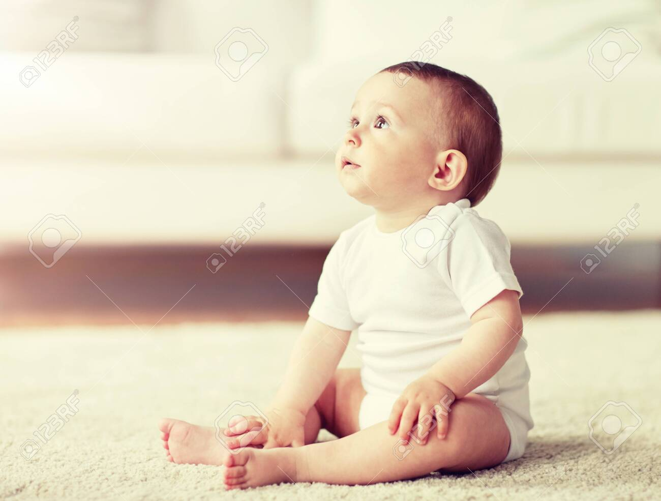 happy baby boy or girl sitting on floor at home - 126742911