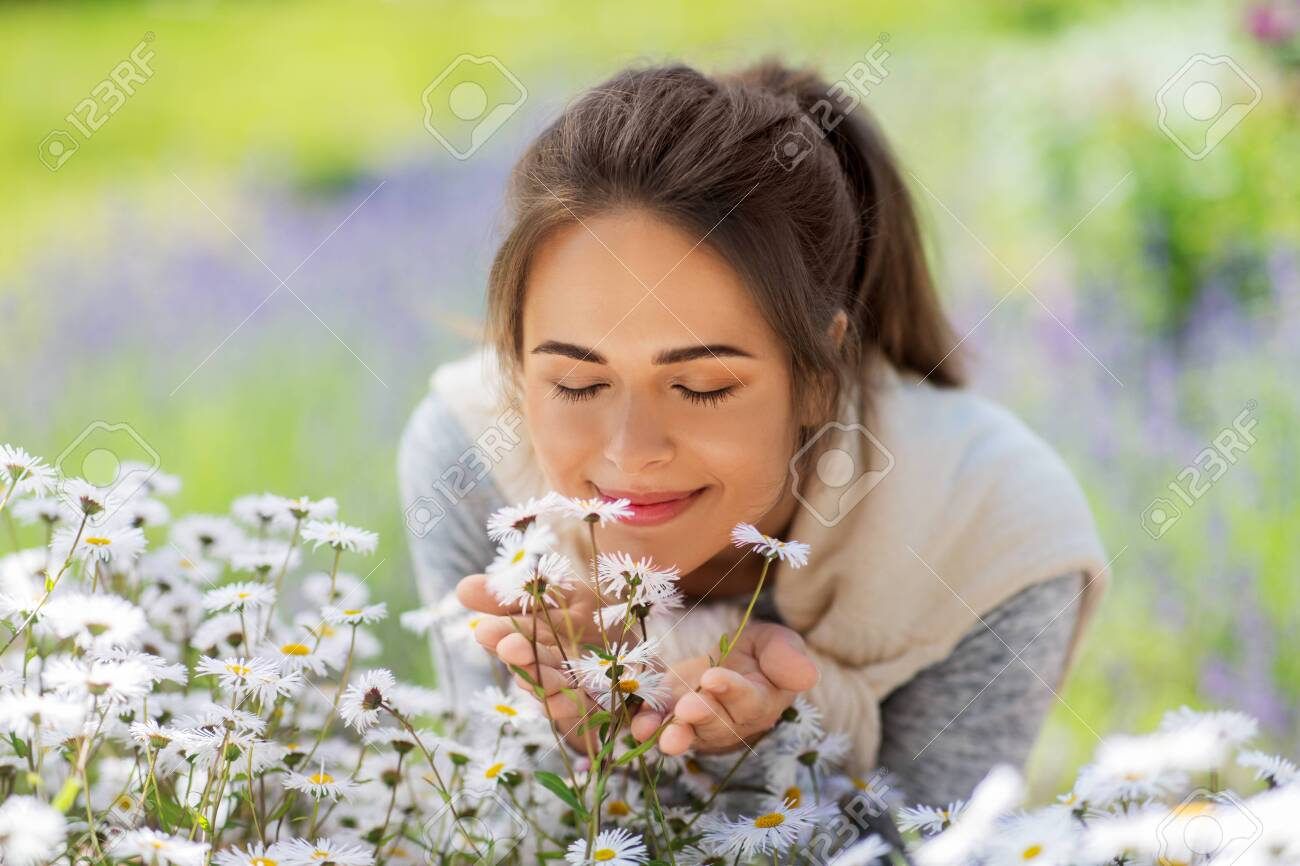 close up of woman smelling chamomile flowers - 128089991