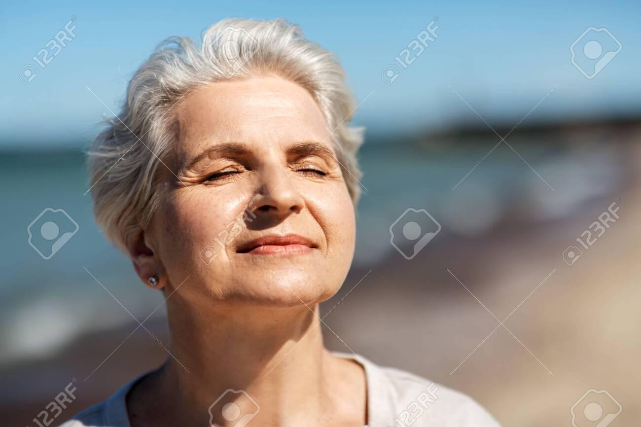 portrait of senior woman enjoying sun on beach - 128860456