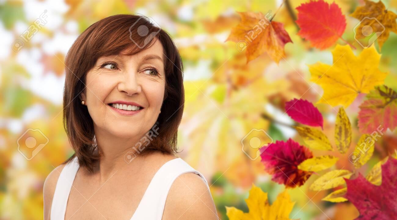 portrait of happy senior woman over autumn leaves - 128863352