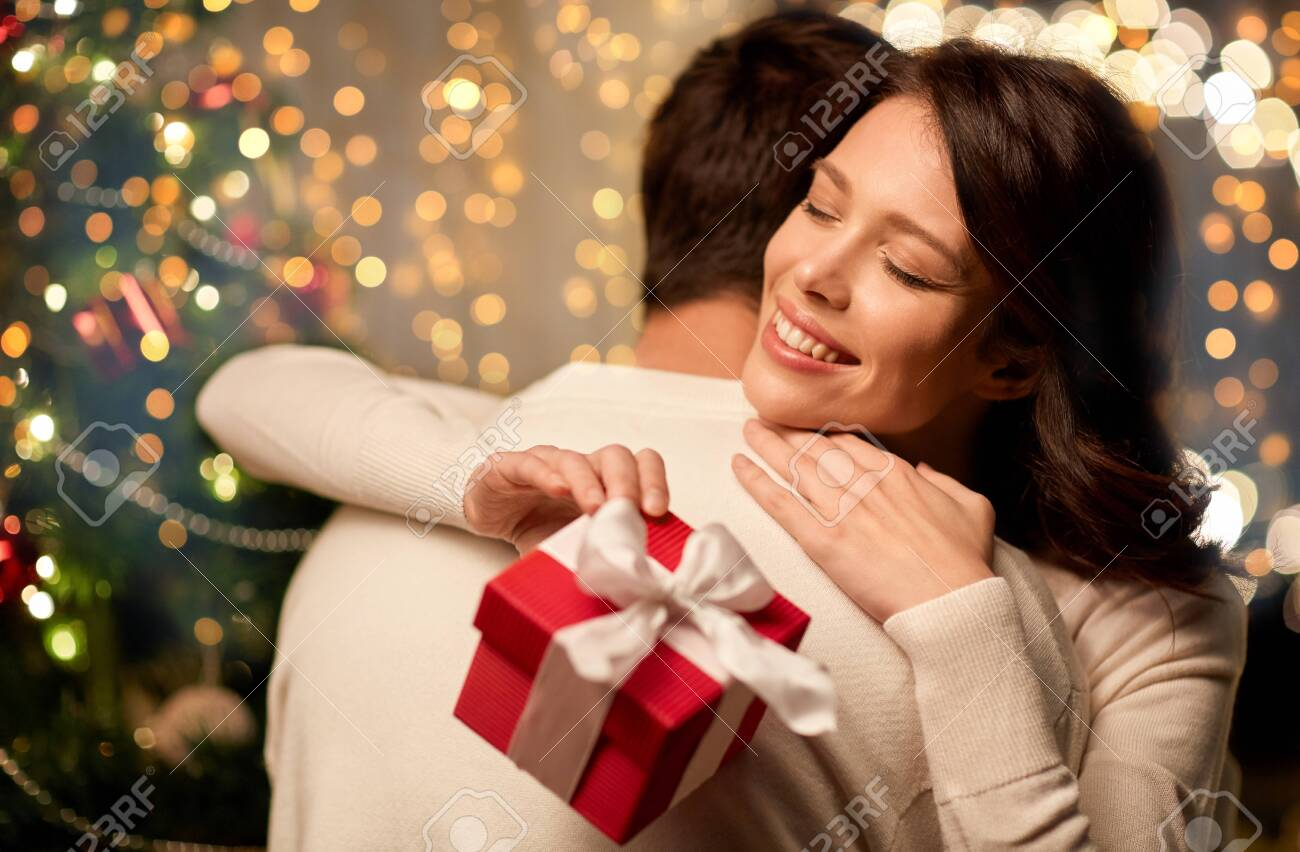 happy couple with christmas gift hugging at home - 131718762