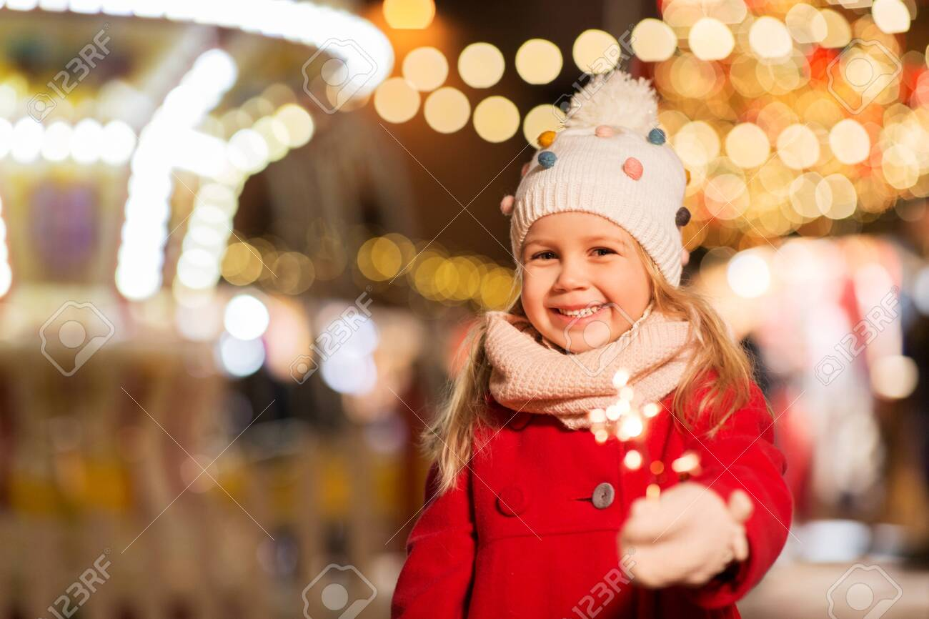 happy girl with sparkler at christmas market - 129631671