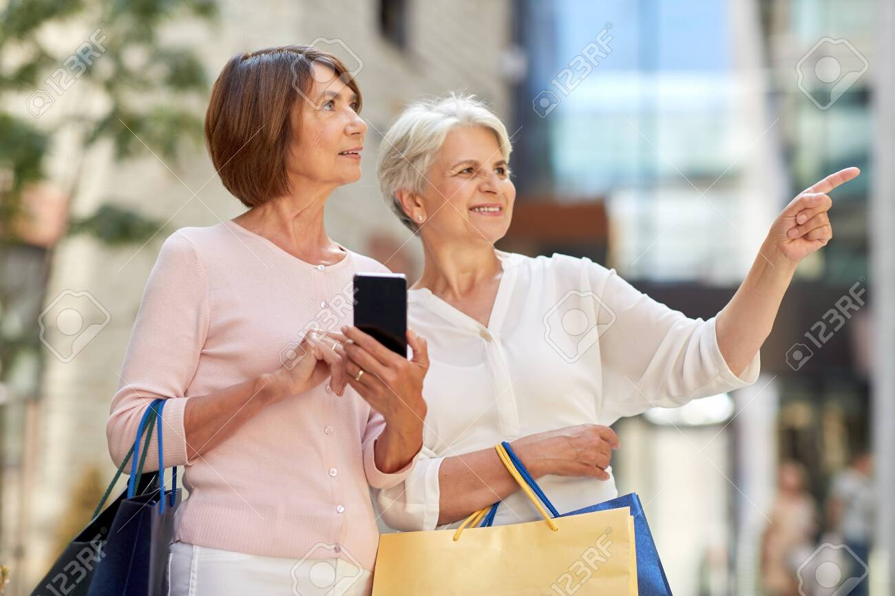 old women with shopping bags and cellphone in city - 129601733