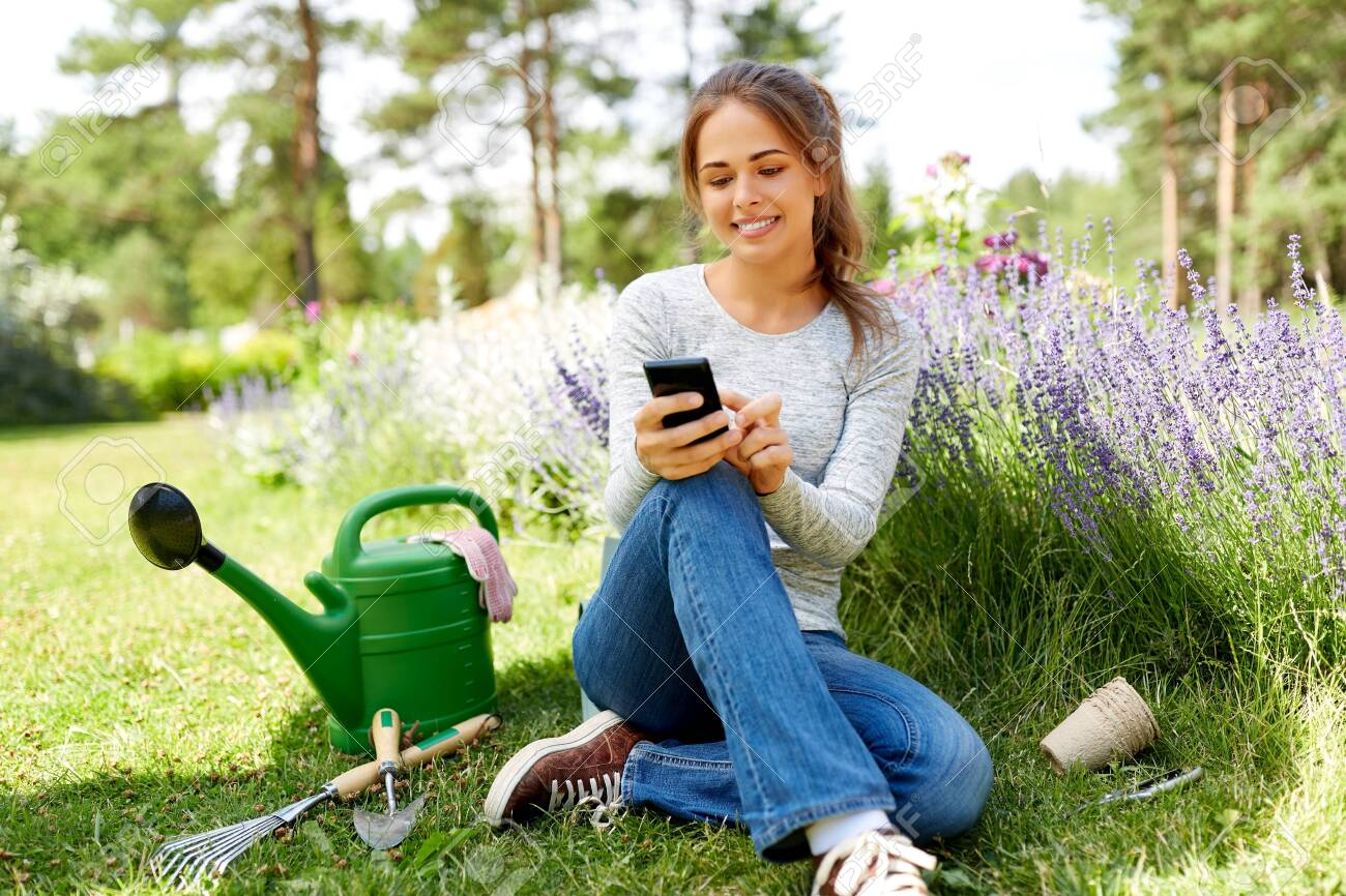 woman with smartphone and garden tools in summer - 129631797