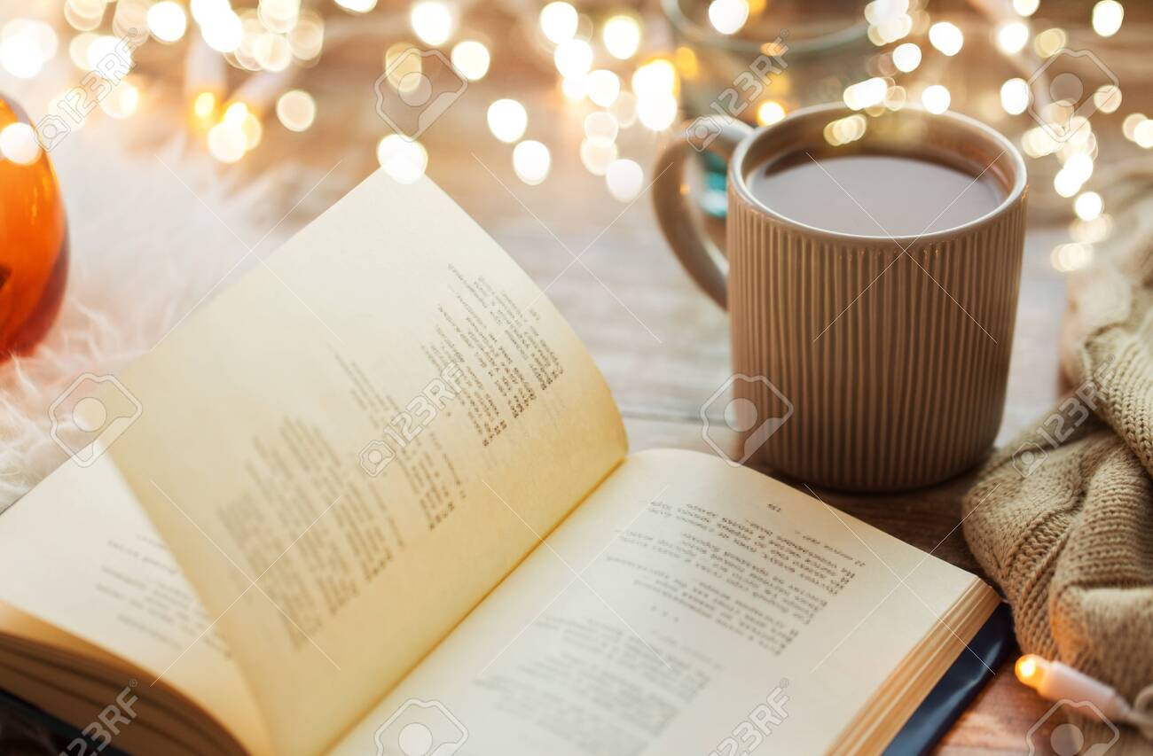 hygge and cozy home concept - book and cup of coffee or hot chocolate on table - 130120813