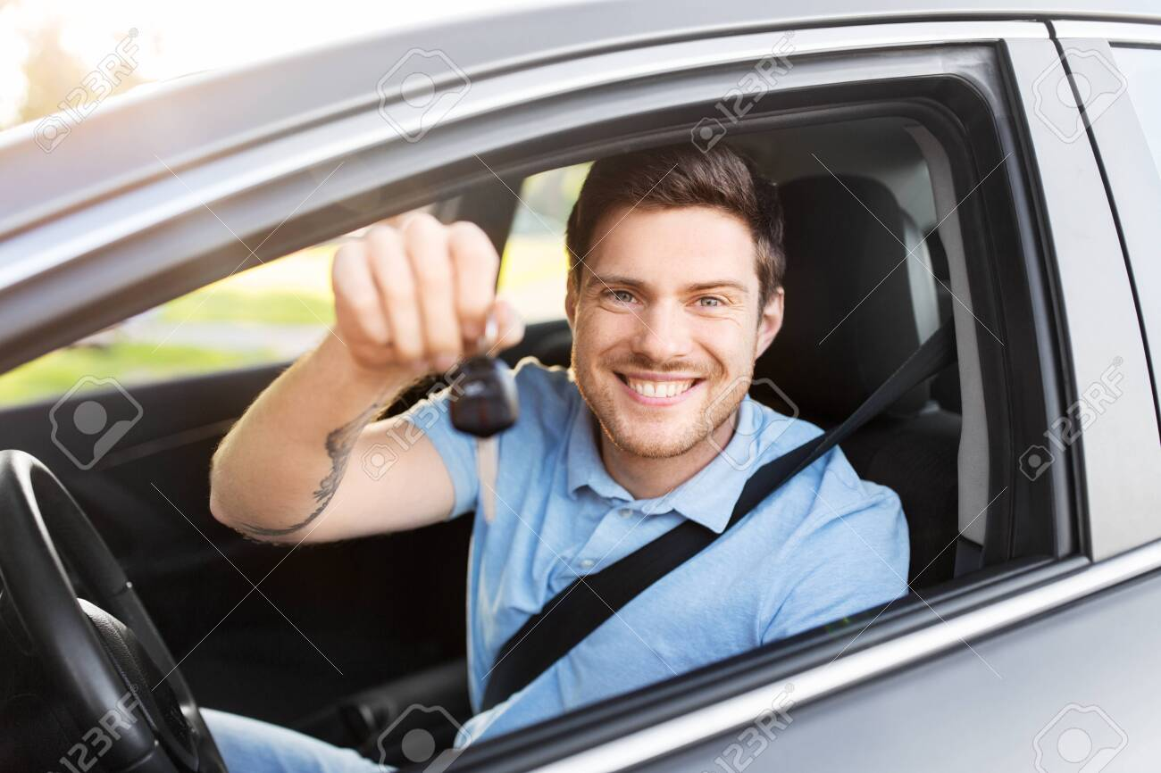 transport, vehicle and ownership concept - happy smiling man or driver with key sitting in car - 130120397