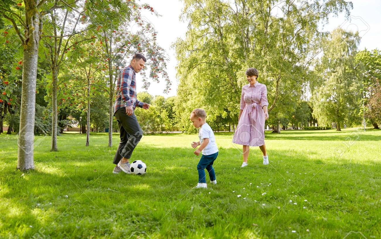 happy family playing soccer at summer park - 130587279