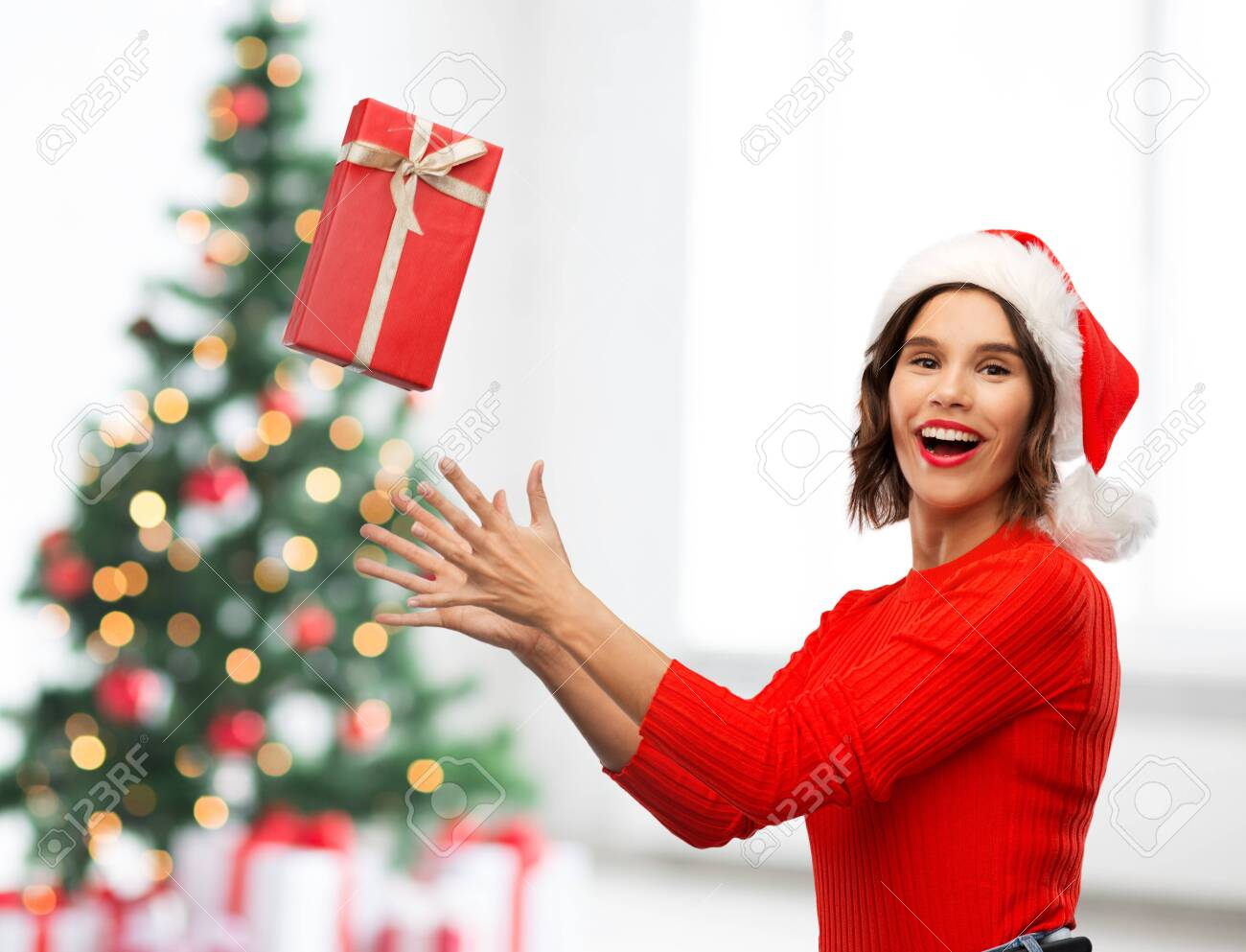 greetings and winter holidays concept - happy smiling young woman in santa helper hat catching red gift box over christmas tree lights background - 133269939
