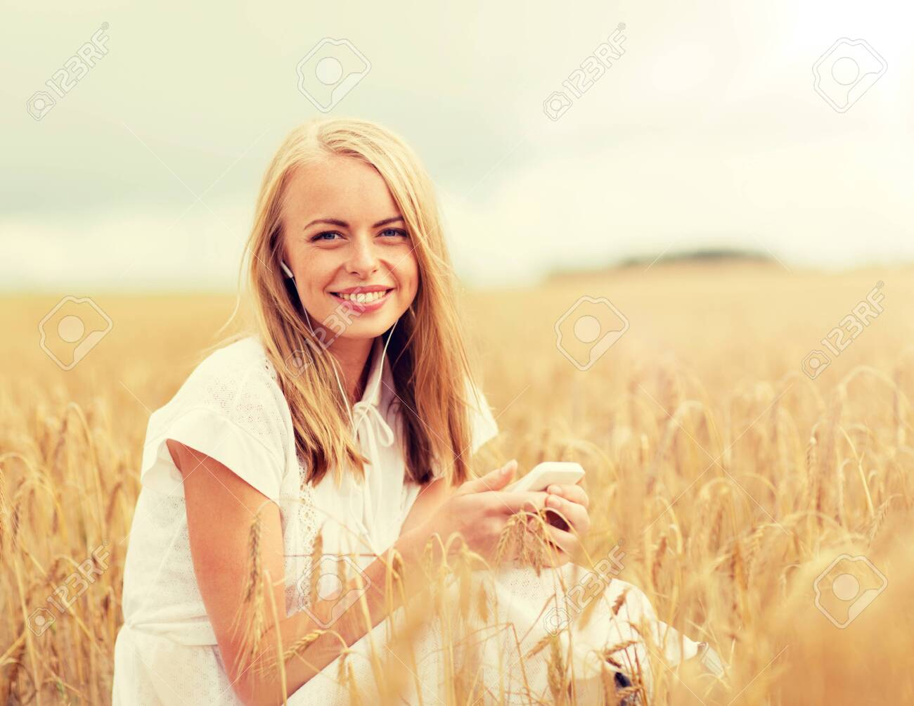 summer holidays, vacation, technology and people concept - smiling young woman in white dress with smartphone and earphones listening to music on cereal field - 133342957