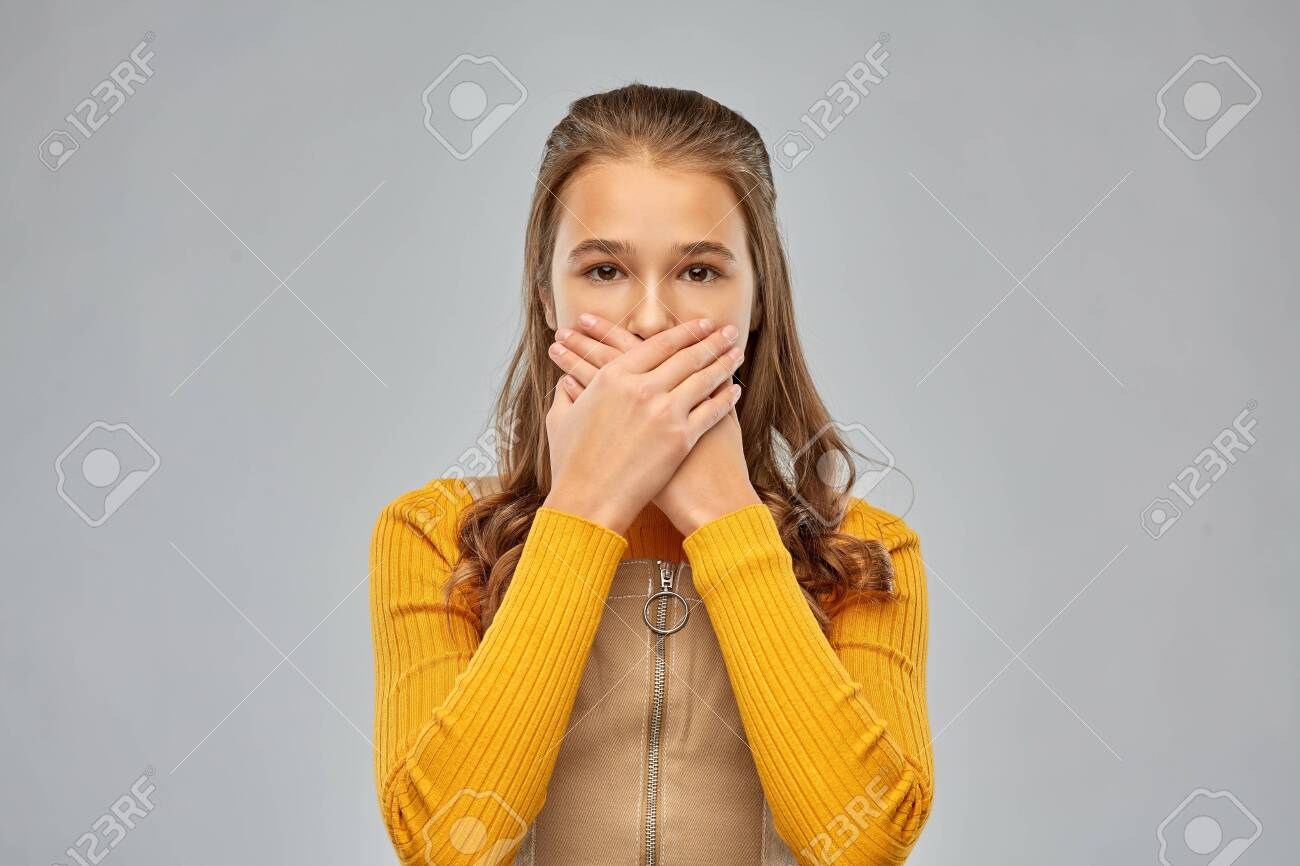 scared teenage girl closing her mouth by hands - 134284818