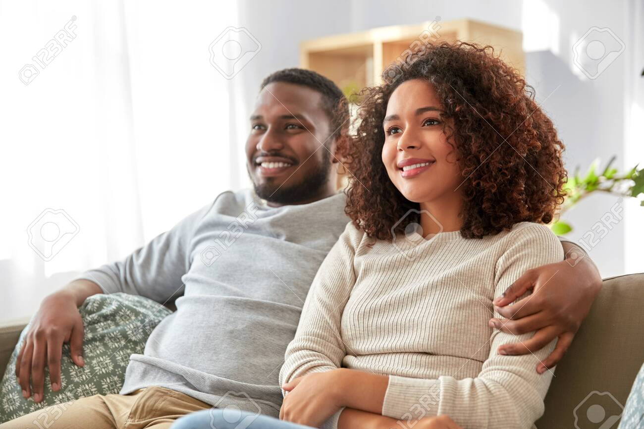 happy african american couple hugging at home - 134285015