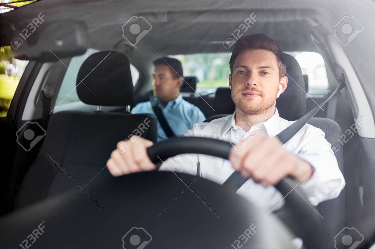 male driver with wireless earphones driving car - 134439802