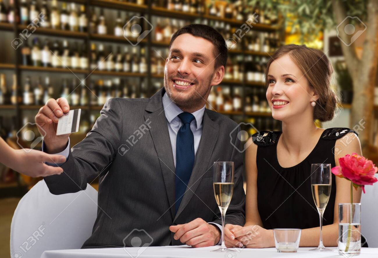 Happy couple paying with credit card at restaurant - 134894243