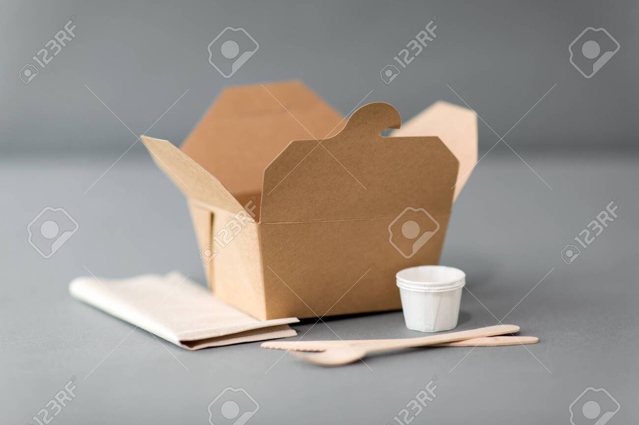 package, recycling and eating concept - disposable box for takeaway food with wooden fork, knife and napkin on table - 134961677