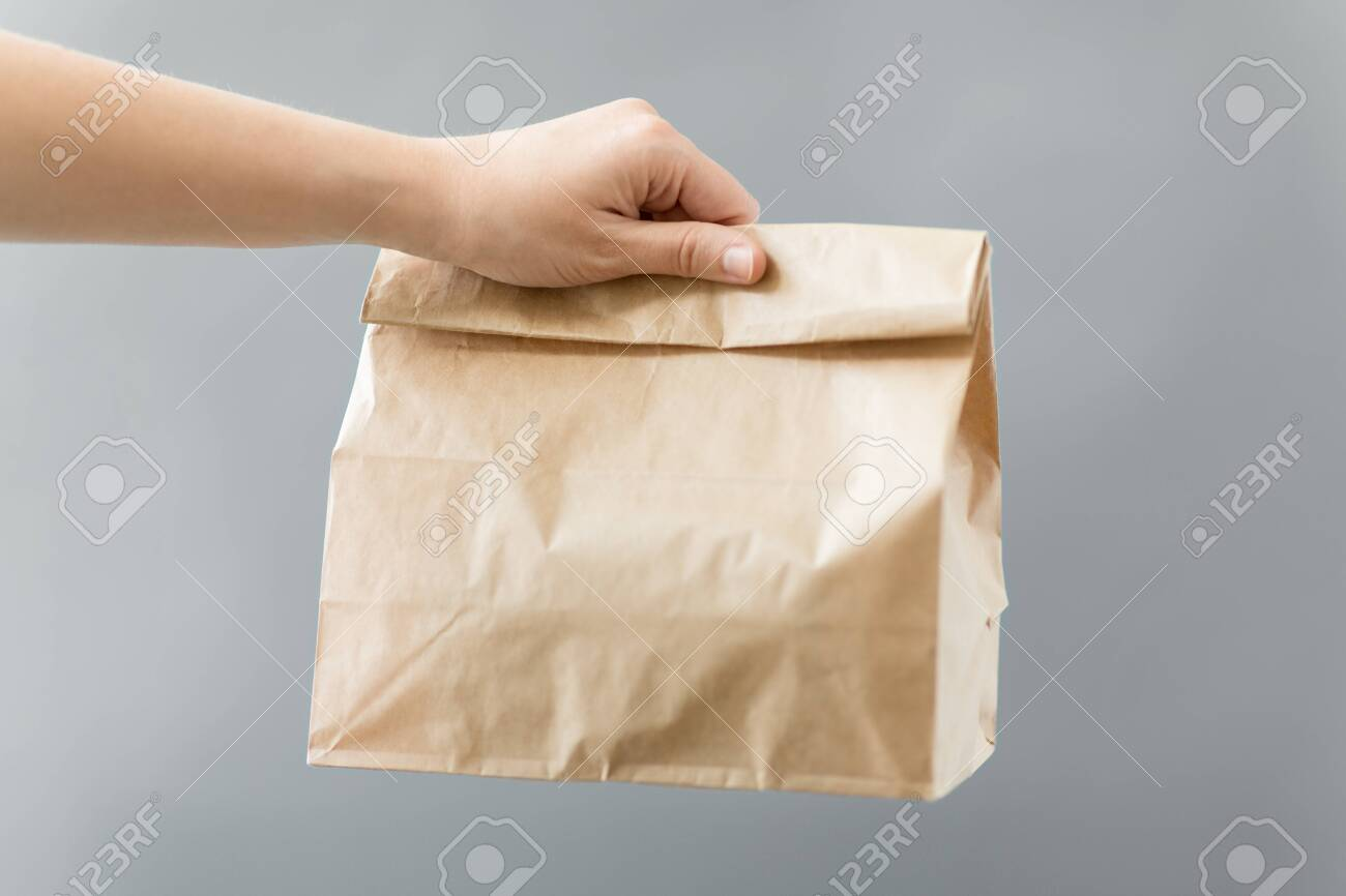 recycling and ecology concept - hand holding disposable brown takeaway food in paper bag with lunch on table - 135399171