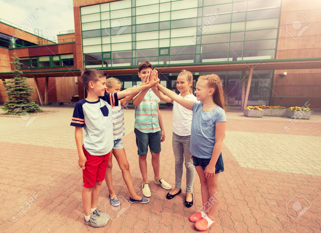 group of children making high five at school yard - 139480270