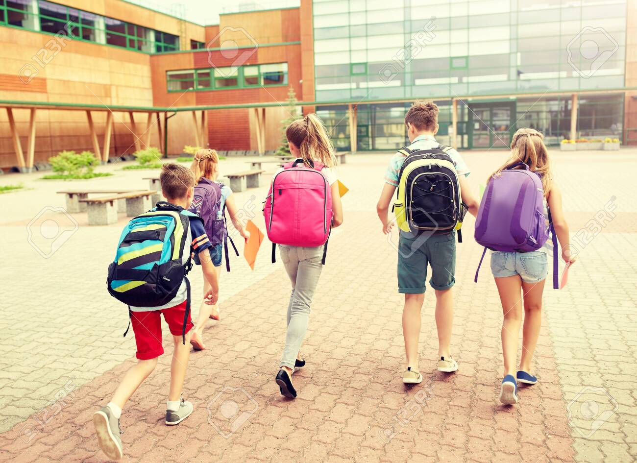 primary education, friendship, childhood and people concept - group of happy elementary school students with backpacks running outdoors - 140533663