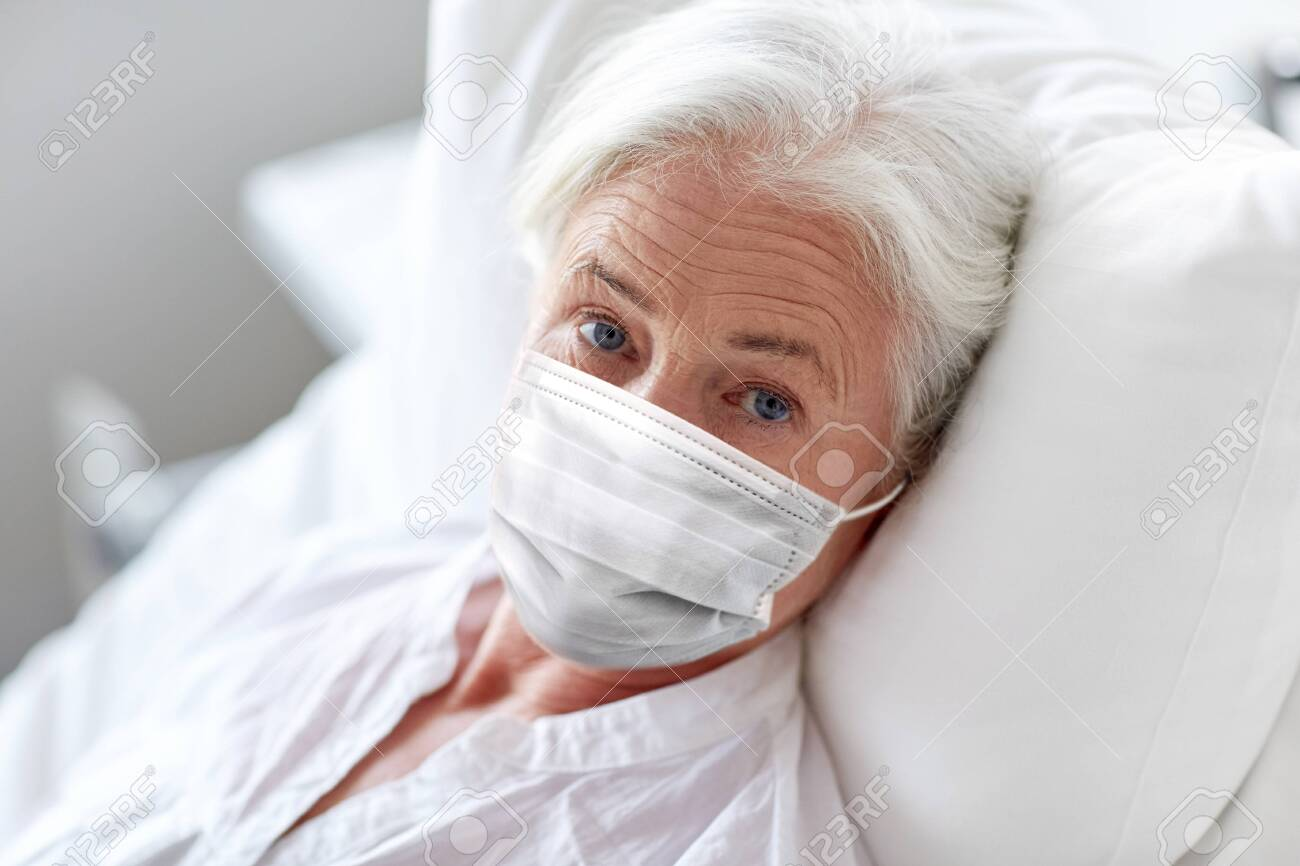 old woman patient in mask lying in bed at hospital - 144229498
