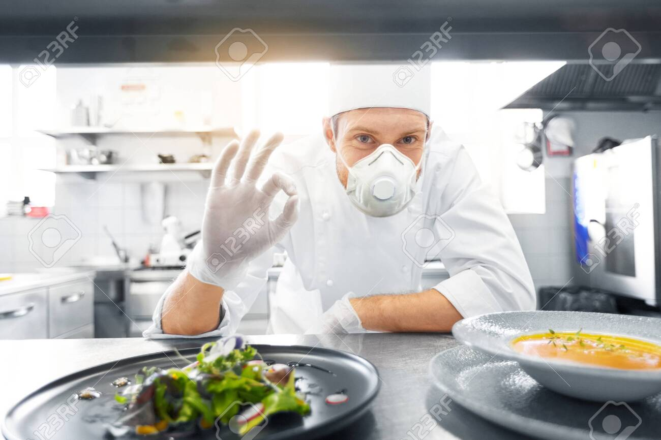 male chef in mask with food at restaurant kitchen - 144229510