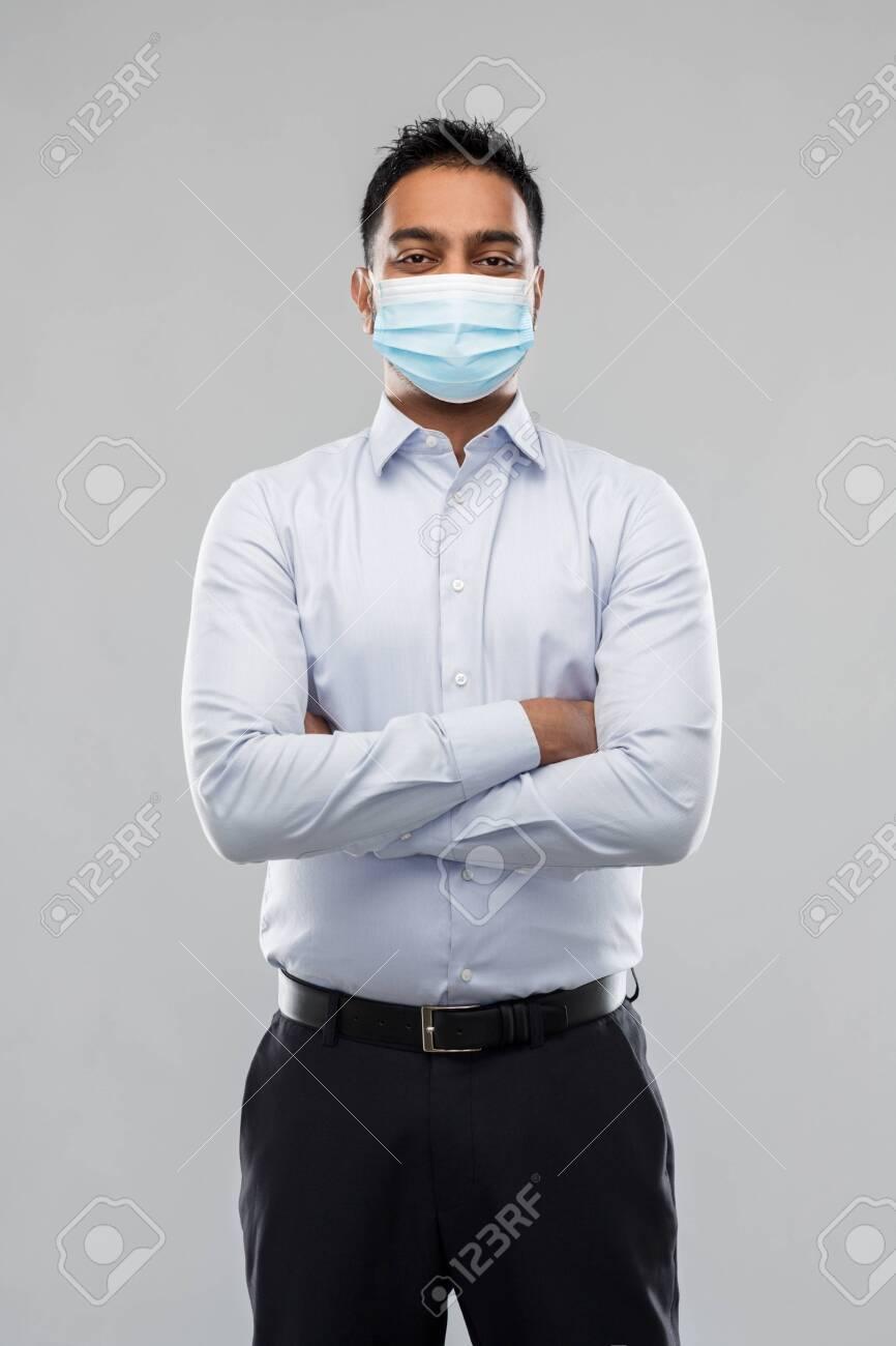 indian businessman in mask over grey background - 146902616