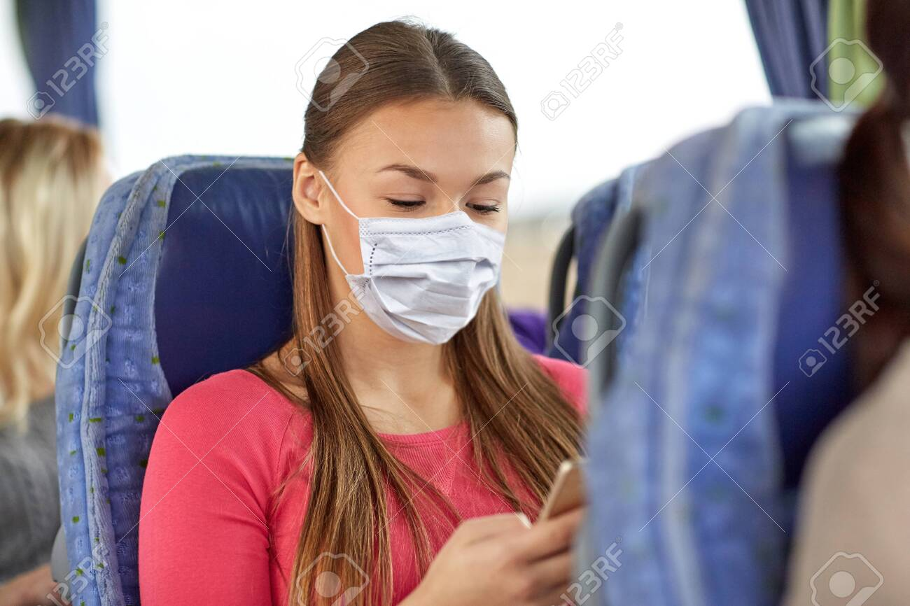 woman in mask using smartphone in travel bus - 147445710