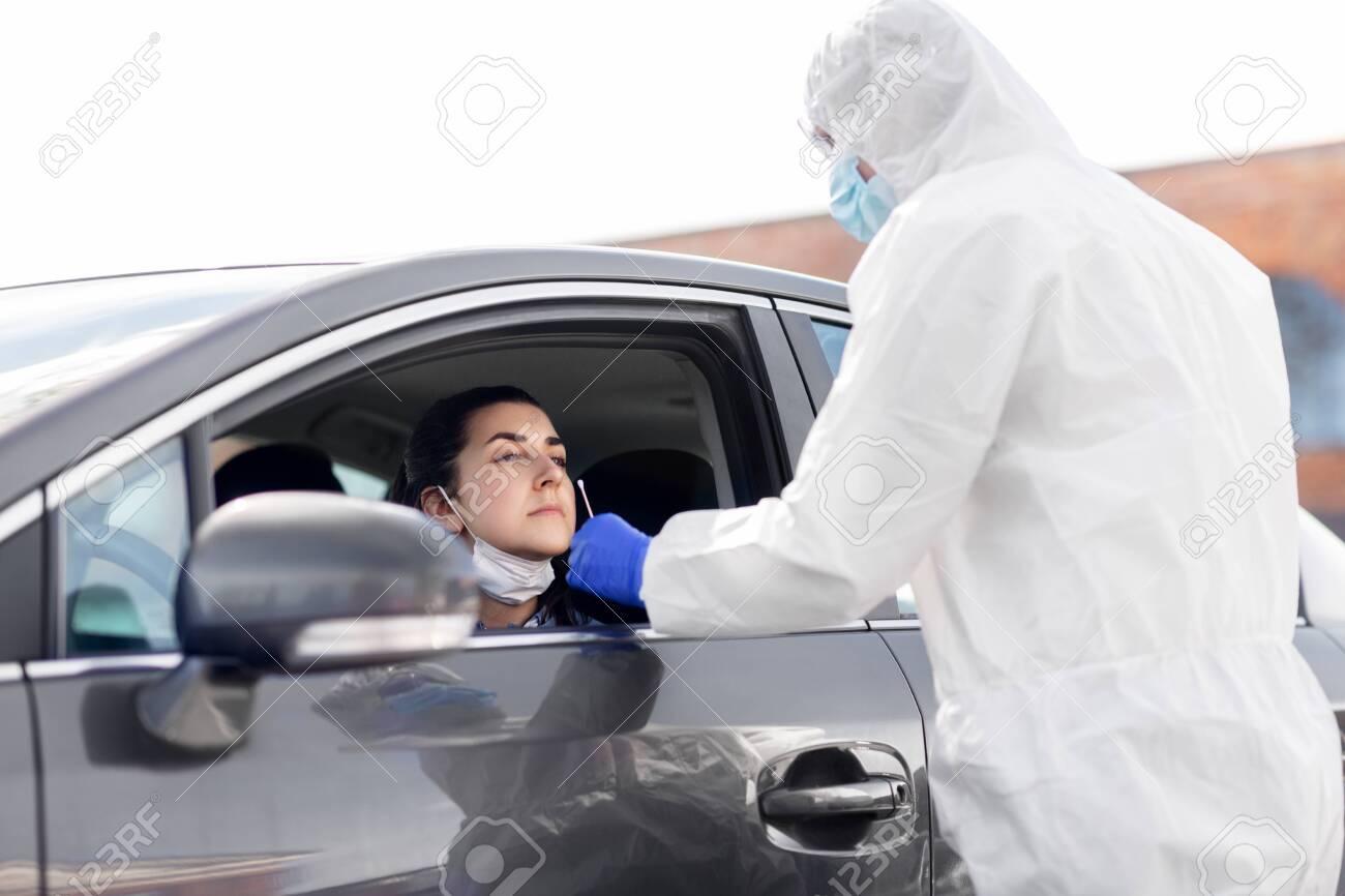 healthcare worker making coronavirus test at car - 150197211