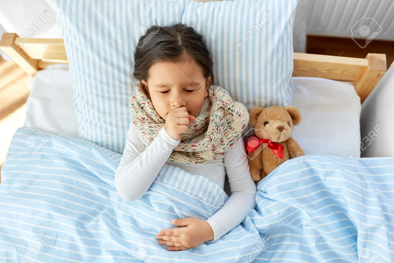 sick coughing girl lying in bed at home - 158480360