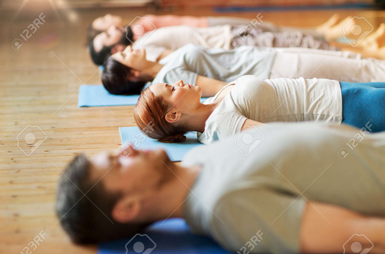 group of people making yoga exercises at studio - 166282556