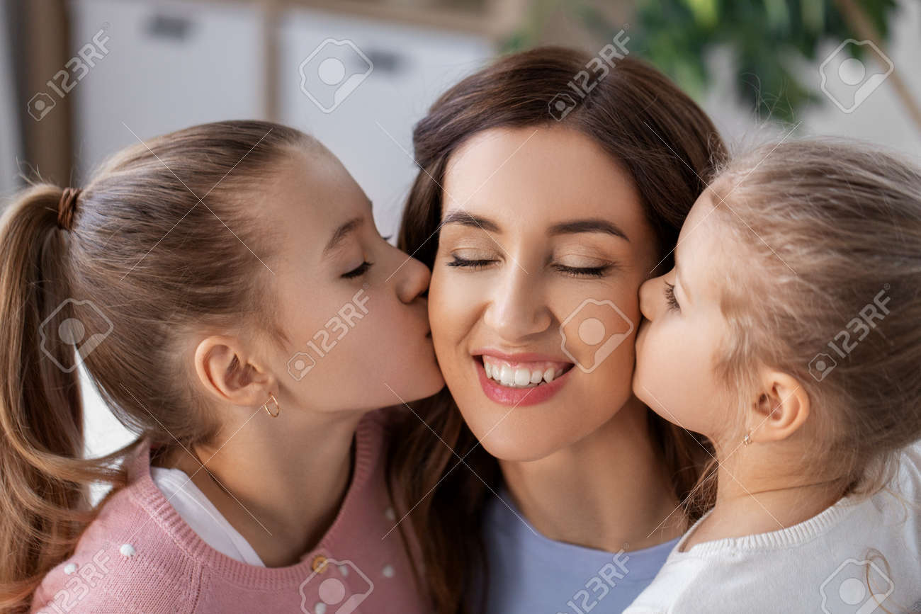 happy mother and two daughters kissing her at home - 167981585