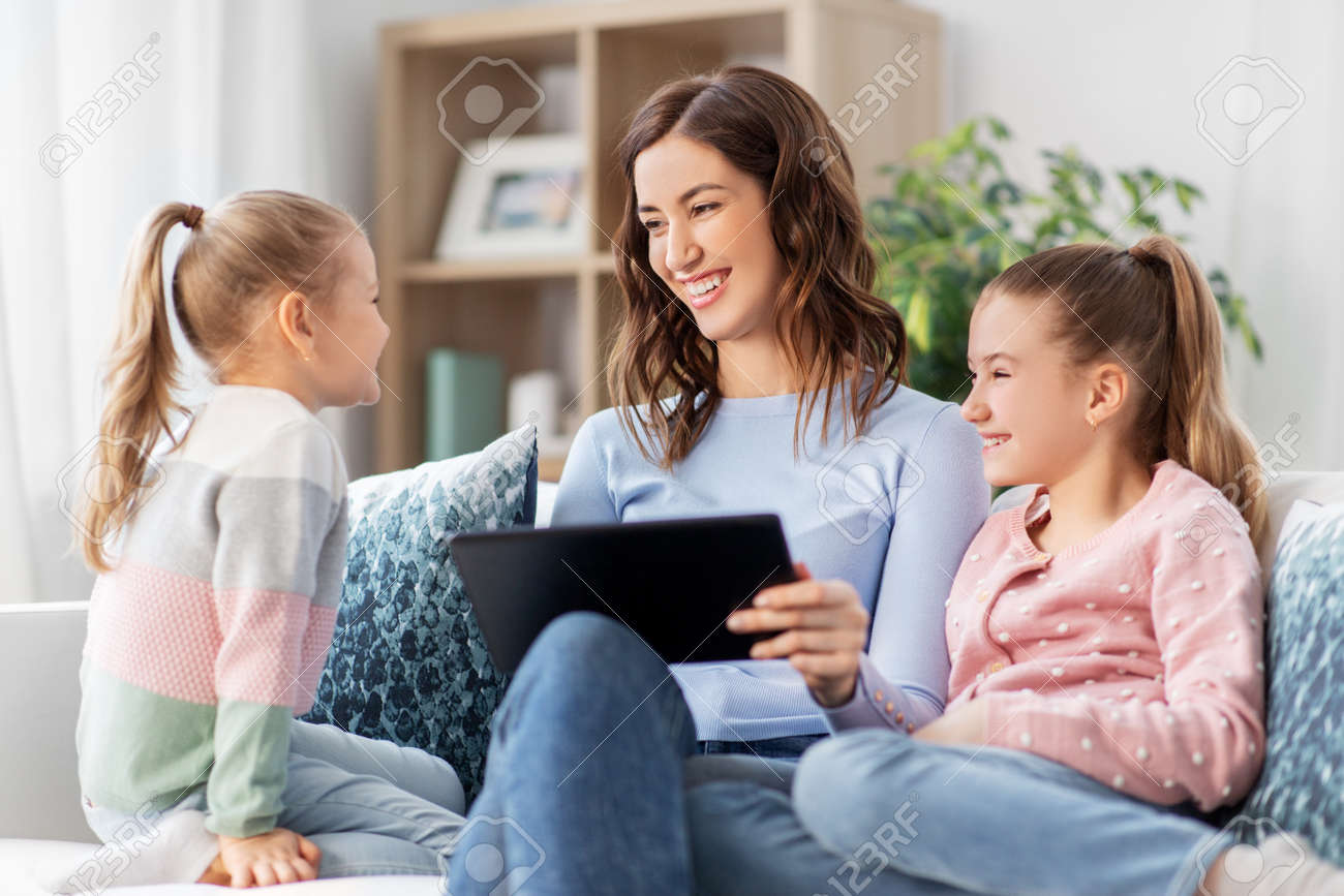 happy mother and daughters with tablet pc at home - 167987260