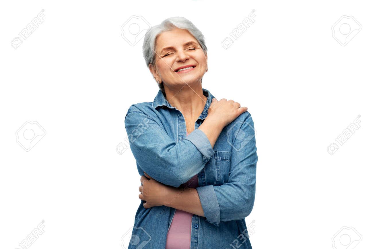 portrait of smiling senior woman in denim shirt - 168426552