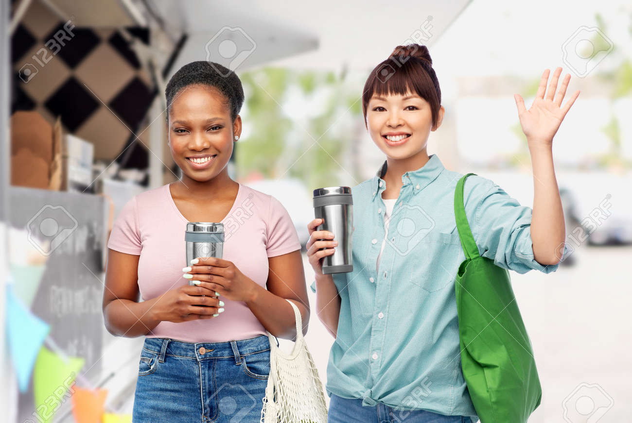 women with tumblers and bags over food truck - 169910281