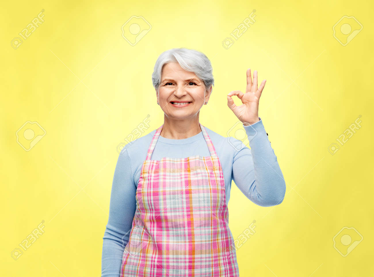 smiling senior woman in apron showing ok gesture - 169910291