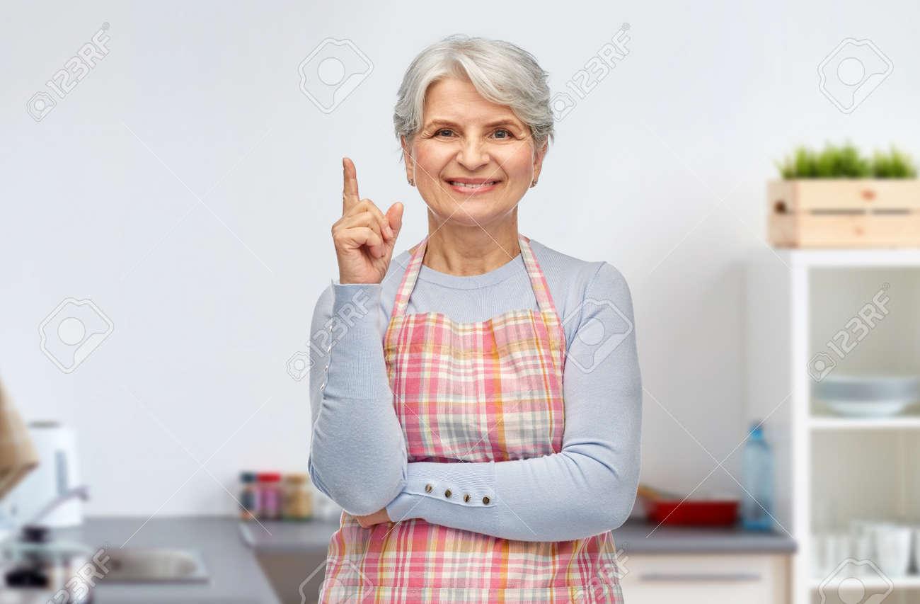 smiling senior woman pointing finger up at kitchen - 169910293