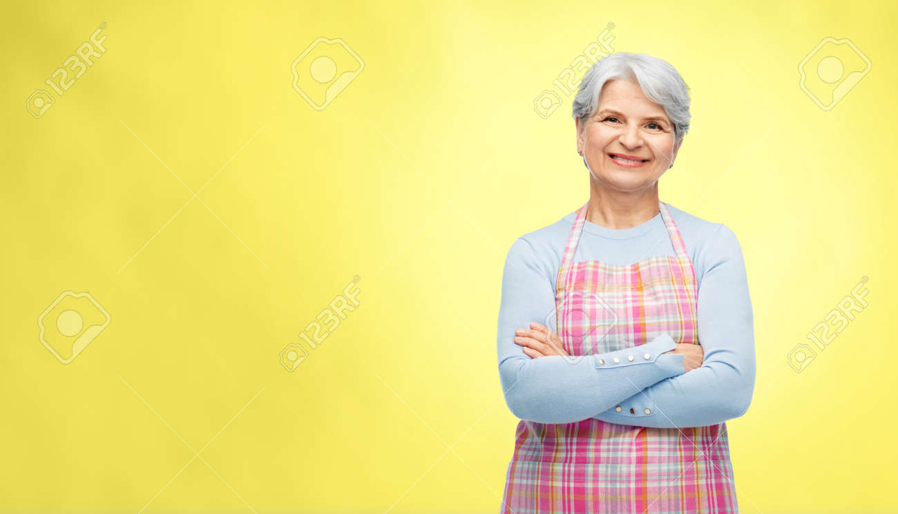 portrait of smiling senior woman in apron - 169910294