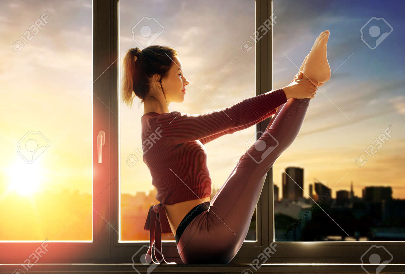 woman doing yoga exercise on window sill at studio - 169910218