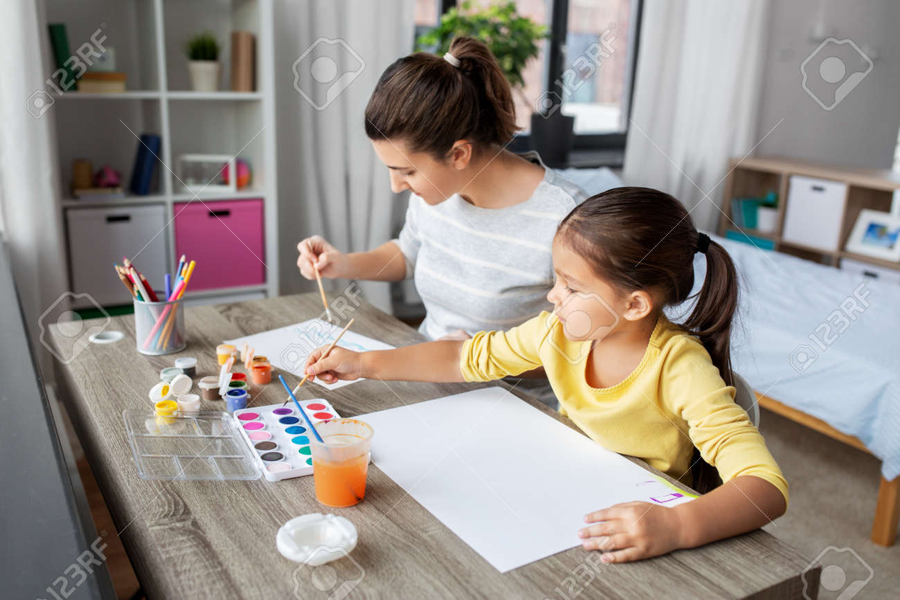 mother with little daughter drawing at home - 169910221