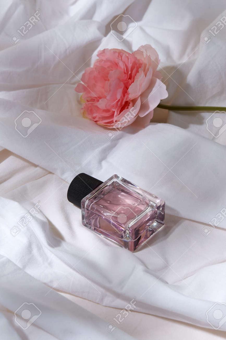 bottle of perfume and flower on white sheet - 169965929