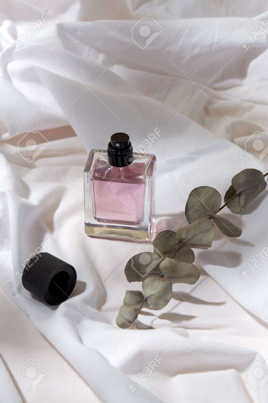 bottle of perfume and on white sheet - 169966593