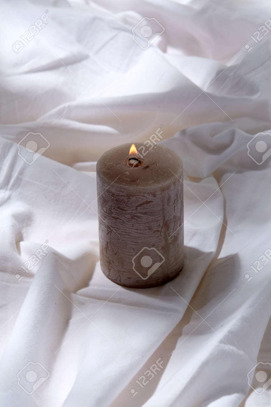 burning aroma candle on white sheet - 169966691