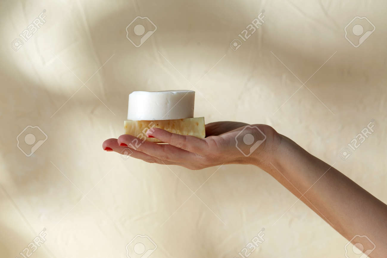 hand holding bar of craft soap on beige background - 169966478