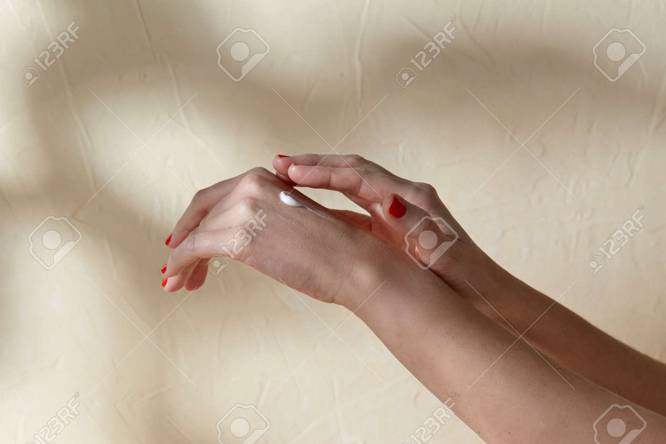 female hands applying moisturizer to skin - 169967132