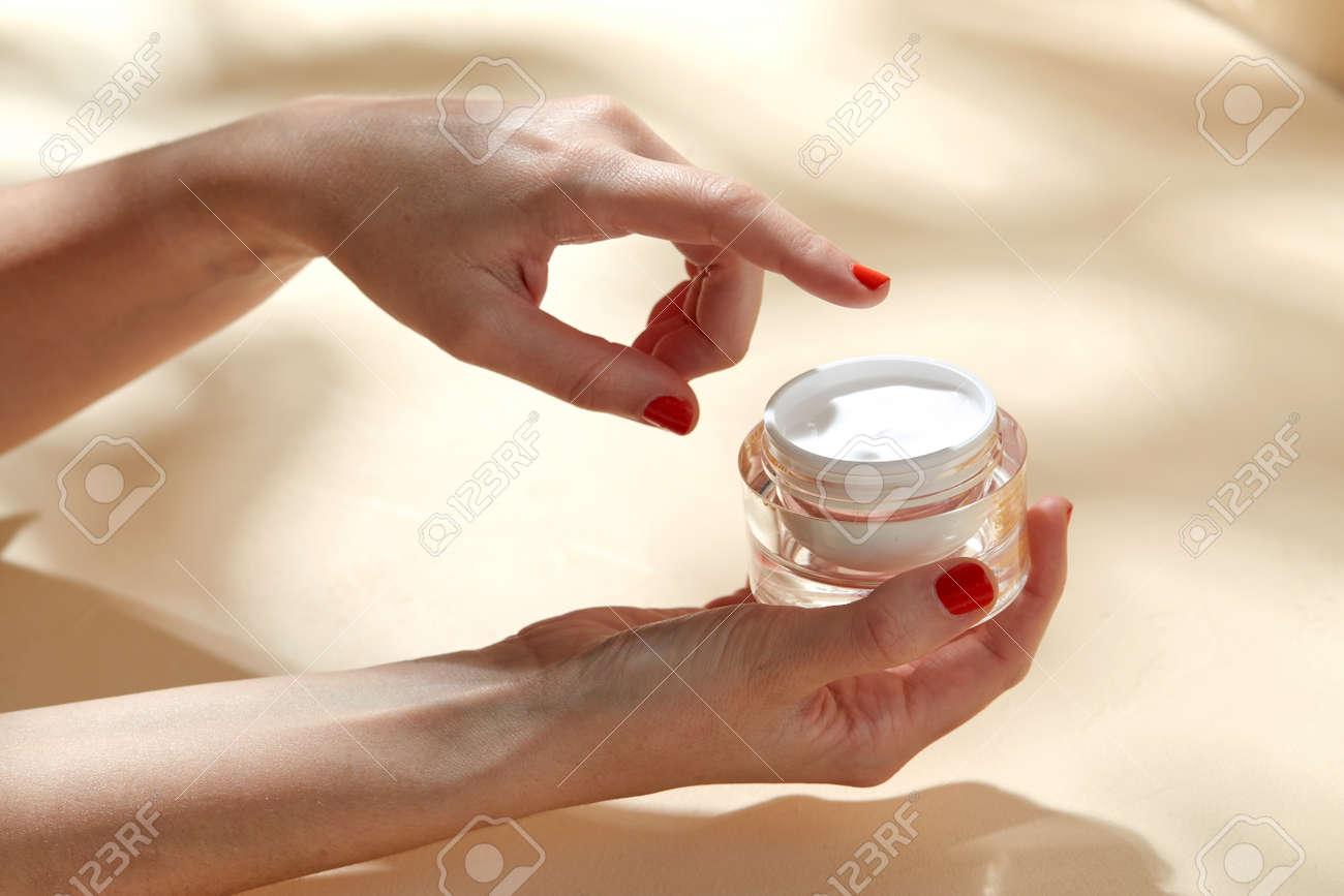female hand holding jar of moisturizer - 169966569