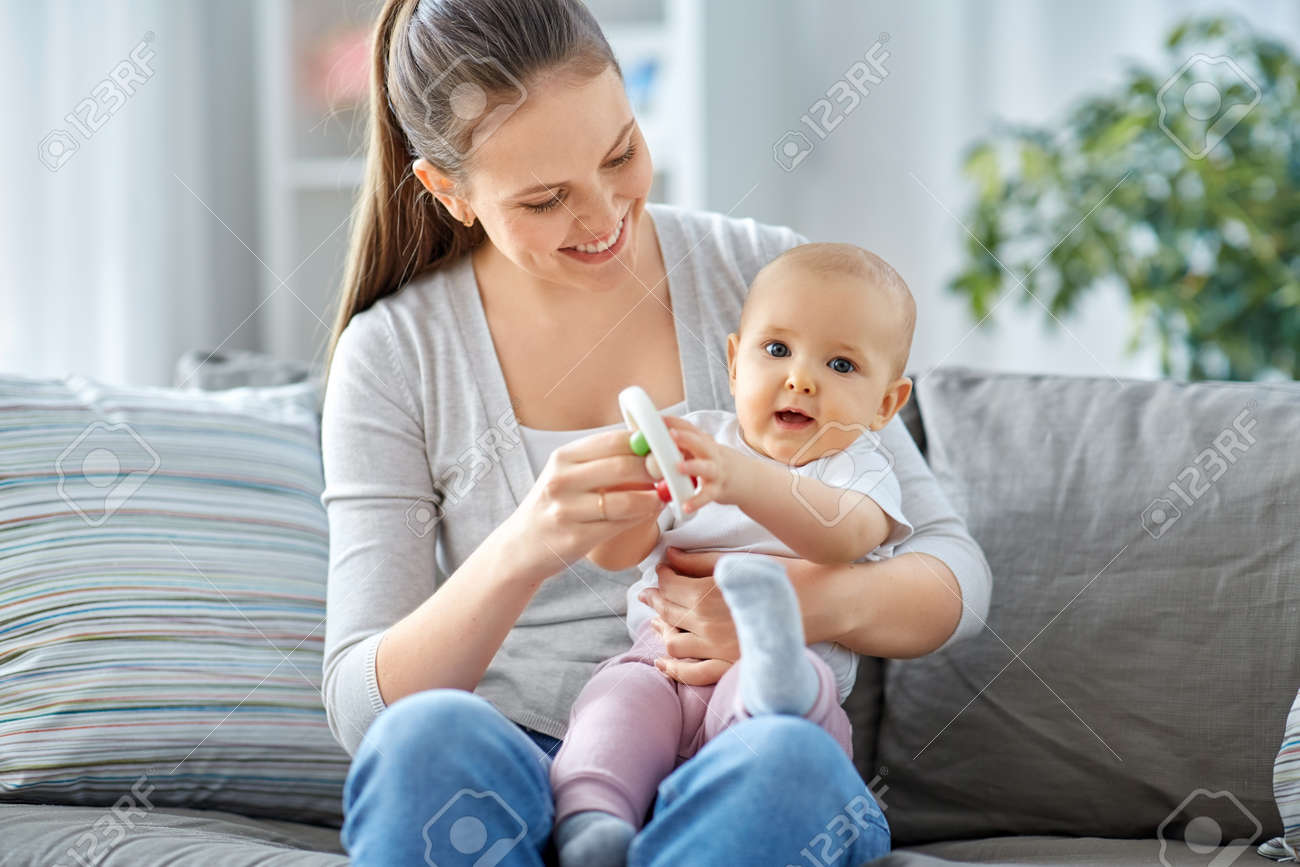 mother and little baby playing with rattle at home - 169965997