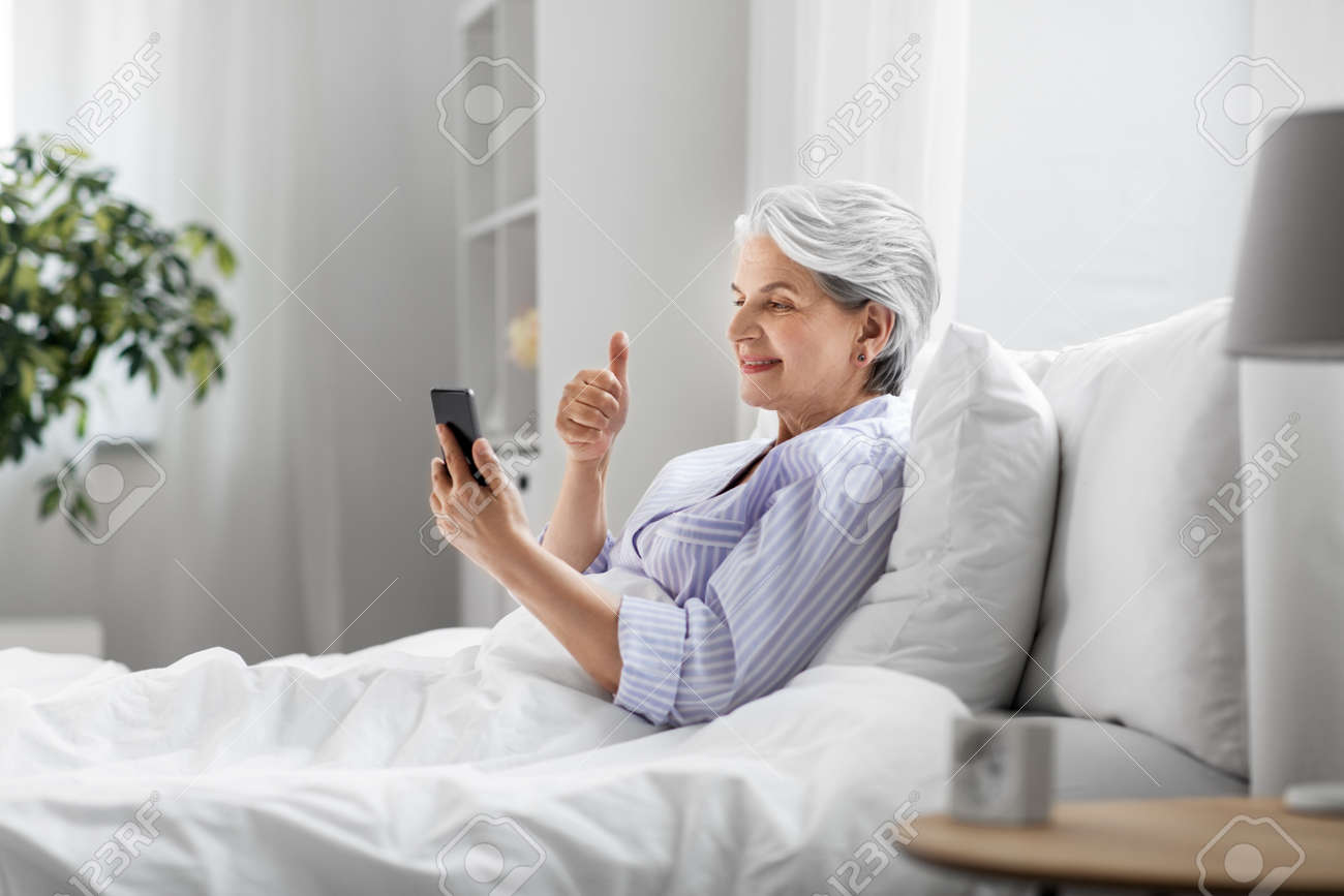 senior woman with phone having video call in bed - 169967844