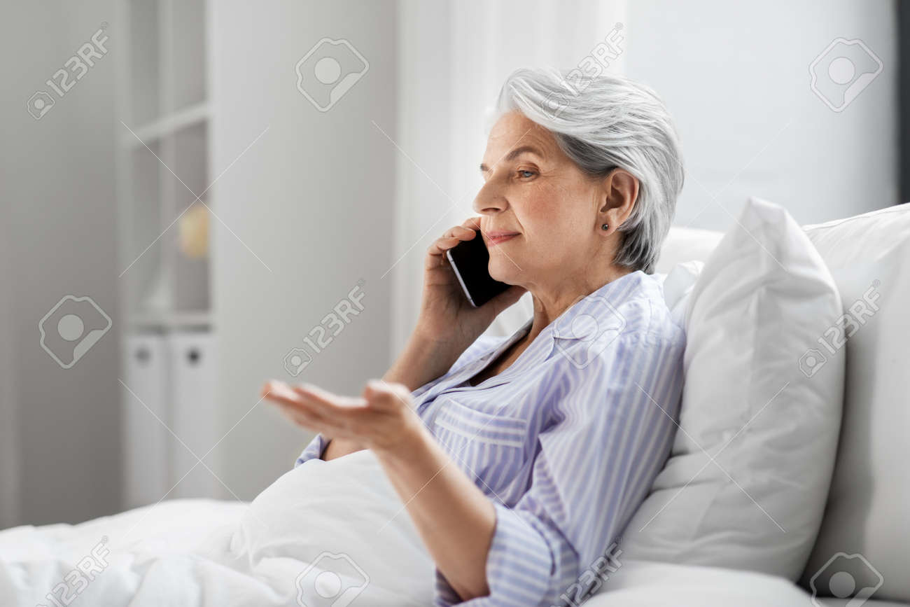senior woman calling on smartphone in bed at home - 169965887