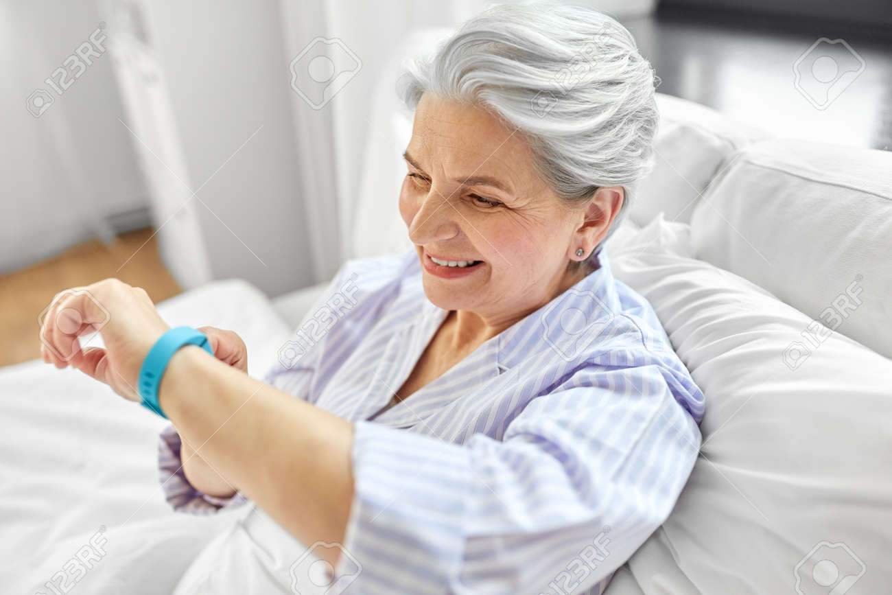 happy old woman with health tracker sitting in bed - 169967654